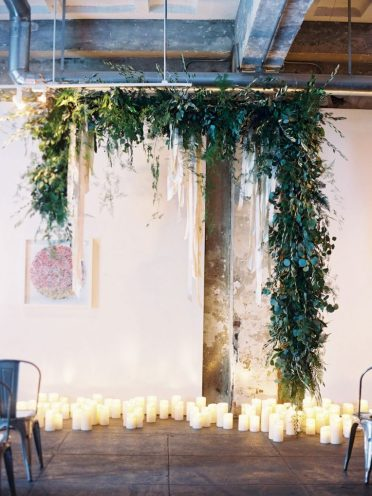Industrial-chic-hanging-greenery-garland-wedding-backdrop-with-candles-768x1019-1