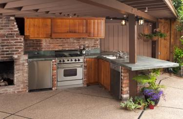 Outdoor-kitchen-with-brick-fireplace-wood-cabinets
