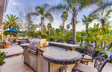 Outdoor-kitchen-with-curved-countertop-and-bar-stool-seating-overlooking-swimming-pool-1