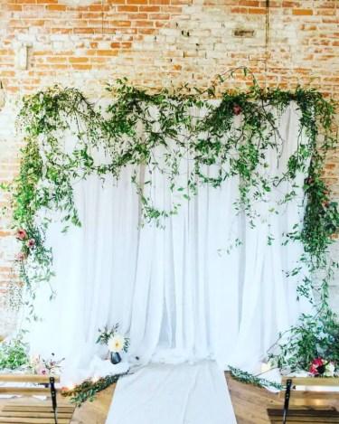 White-draped-wedding-backdrop-with-draped-greenery-768x960-1