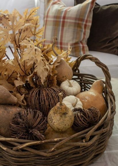 A-basket-with-vine-and-faux-pumpkins-pears-fall-leaves-and-gourds-is-a-rustic-decoration-with-a-strong-natural-feel