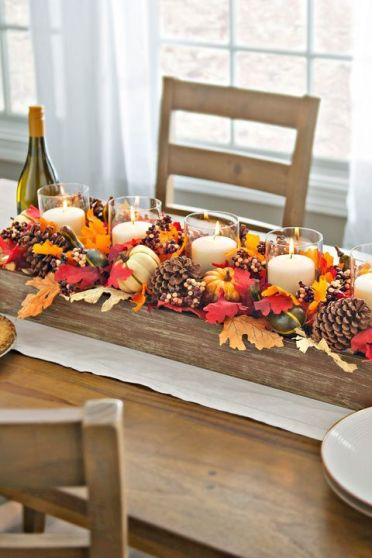A-bright-fall-centerpiece-of-a-wooden-box-fall-leaves-acorns-gourds-and-pillar-candles-in-glasses