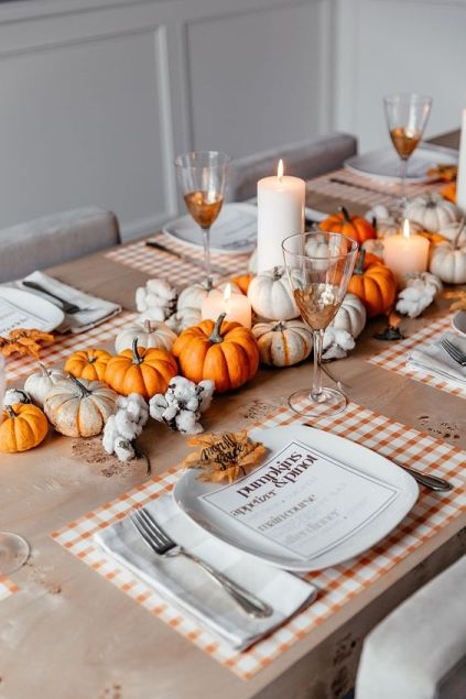 A-bright-fall-tablescape-with-plaid-placemats-a-bold-fall-centerpiece-of-neutral-and-orange-pumpkins-plus-candles