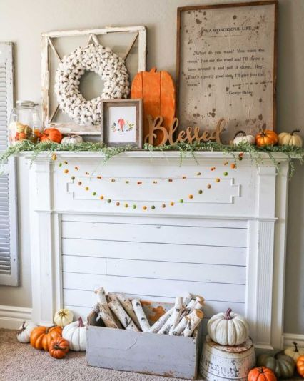 A-bright-rustic-flal-mantel-with-colorful-pompom-garlands-a-crate-with-birch-branches-lots-of-pumpkins-signs-and-a-cotton-wreath-1