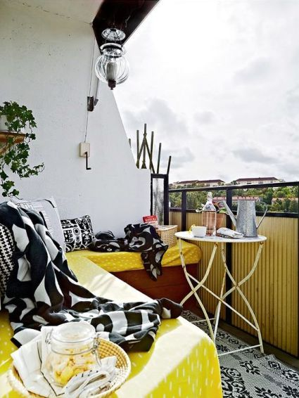 A-bright-summer-balcony-with-a-corner-bench-and-yellow-black-and-white-textiles-a-shabby-chic-table-and-a-potted-plant