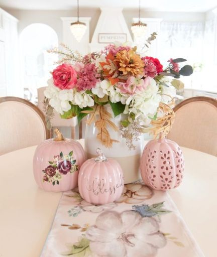 A-chic-and-bright-fall-flower-arrangement-of-white-pink-rust-blooms-and-greenery-and-pink-faux-pumpkins