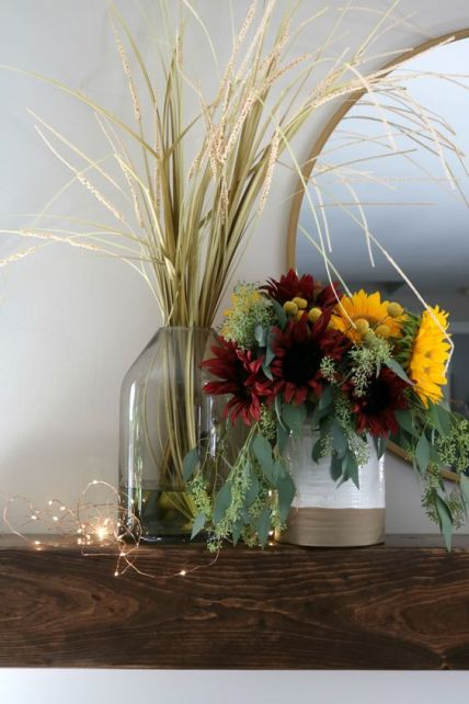 A-chic-fall-faux-flower-arrnagement-with-lots-of-eucalyptus-burgundy-and-yellow-blooms-plus-a-grass-arrangement