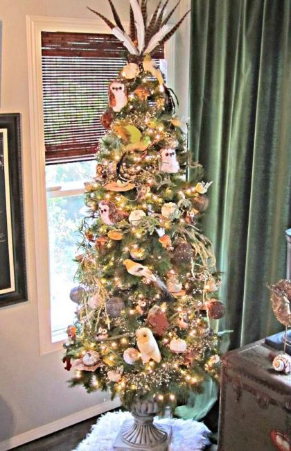 A-fall-tree-with-owls-lights-pumpkins-vine-balls-branches-ribbons-and-feathers-on-the-top