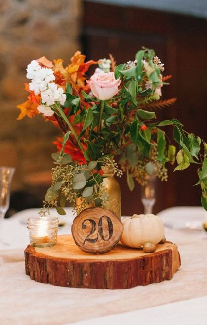 A-fall-wedding-centerpiece-of-a-wood-slice-pumpkins-candles-and-bright-fall-blooms-in-a-gold-jar