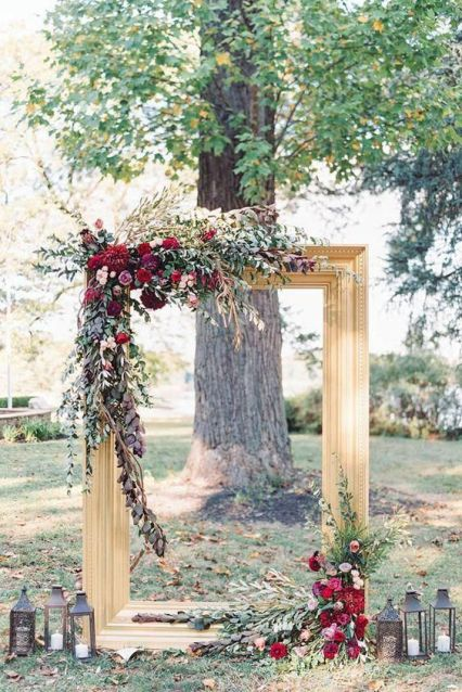 A-gold-frame-decorated-with-greenery-foliage-and-burgundy-blooms-plus-candle-lanterns-for-an-outdoor-fall-ceremony