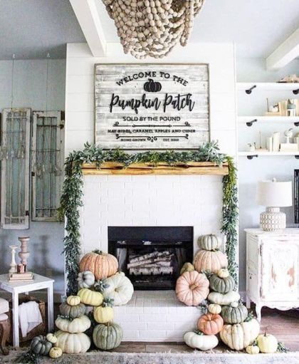 A-modern-farmhouse-mantel-with-stacks-of-heirloom-pumpkins-a-greenery-wreath-and-a-large-rustic-sign