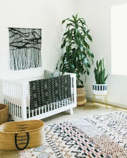 A-monochromatic-boho-nursery-with-a-black-macrame-hanging-a-printed-rug-a-folksy-print-blanket-and-potted-plants
