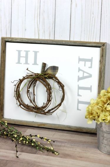 A-non-typical-fall-sign-in-a-reclaimed-wooden-frame-a-twig-pumpkin-attached-and-yellow-blooms-next-to-it