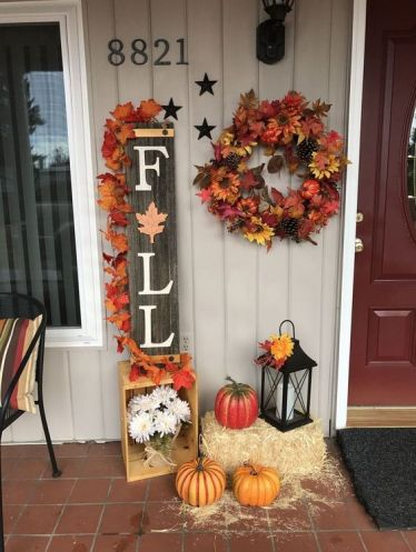 A-reclaimed-wood-fall-sign-topped-with-bright-fake-leaves-faux-pumpkins-a-wreath-hay-and-a-lantern