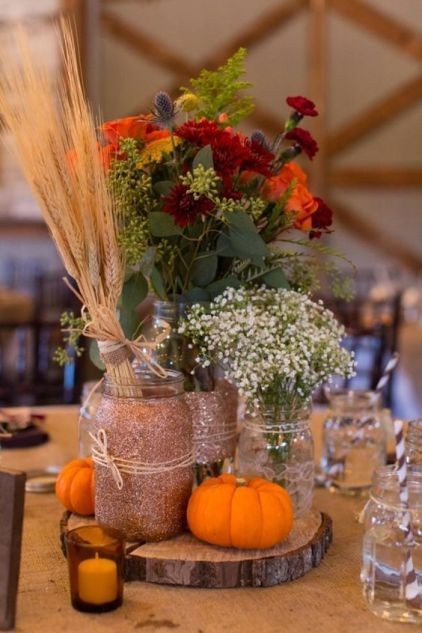 A-rustic-fall-centerpiece-of-a-wood-slice-pumpkins-candles-bright-blooms-babys-breath-and-a-wheat-bundle