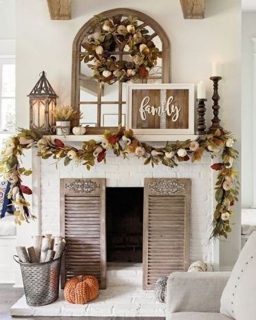 A-rustic-fall-mantel-with-dried-fall-leaves-and-pumpkins-candles-in-wooden-candle-holders-wheat-arrangements-and-a-rustic-sign