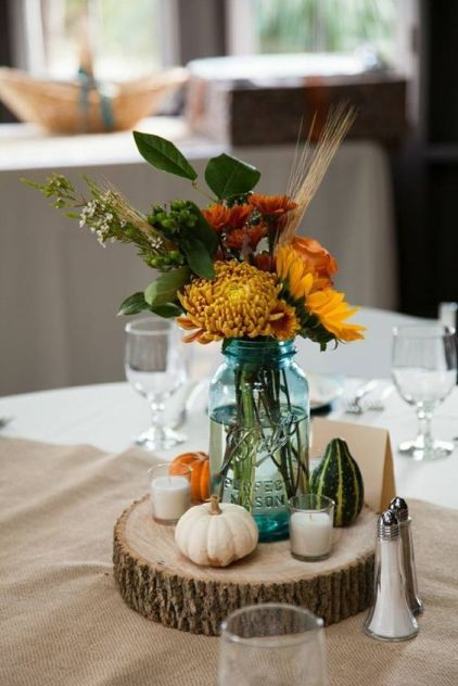 A-rustic-fall-wedding-centerpiece-of-a-wood-slice-candles-pumpkins-and-bright-fall-blooms-and-wheat-in-a-jar
