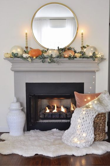 A-simple-contemporary-fall-mantel-done-with-greenery-and-pumpkins-of-muted-colors-plus-lights-all-over-it