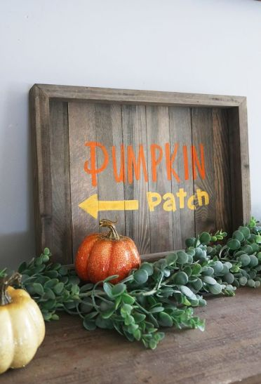 A-stained-fall-sign-with-colorful-letters-fresh-greenery-and-colorful-faux-pumpkins