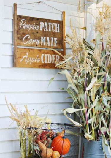 A-stained-wooden-sign-with-white-letters-and-a-wire-basket-with-fall-veggies-and-greenery-for-a-fall-touch