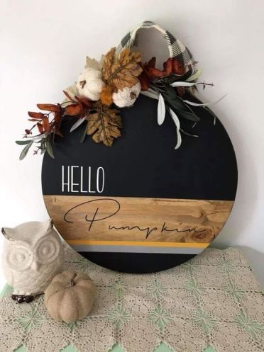 A-stylish-round-fall-sign-done-with-staining-and-black-paint-topped-with-leaves-yarn-pumpkins-and-plaid-ribbon