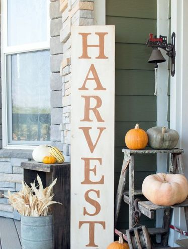 A-tall-harvest-sign-corn-husks-in-a-bucket-and-various-colorful-pumpkins-around-for-a-fall-feel