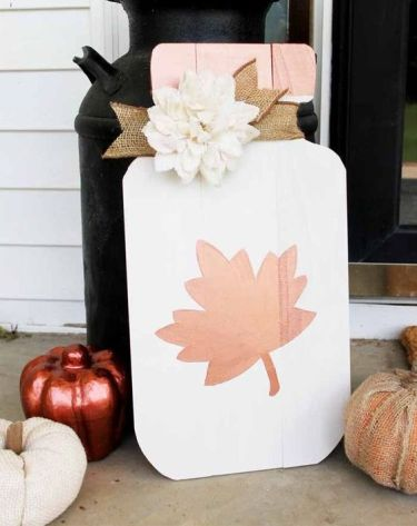 A-white-msaon-jar-with-leaf-fall-sign-with-a-burlap-ribbon-and-a-faux-white-flower-for-the-fall