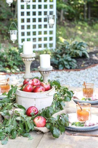 A-wooden-basket-with-red-apples-and-lush-foliage-a-couple-of-candles-in-wooden-candleholders-for-a-fall-centerpiece