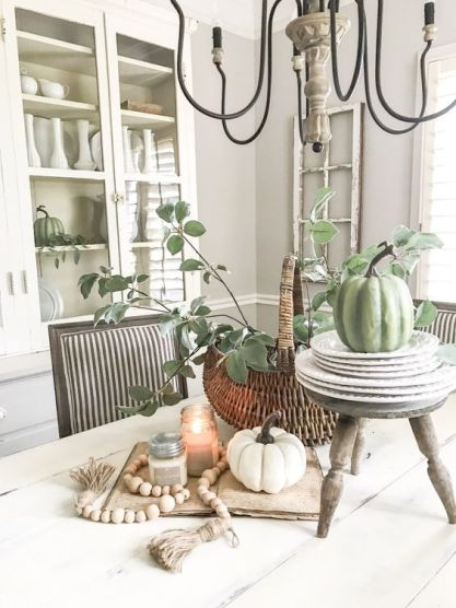 Fall-kitchen-decor-with-white-and-green-pumpkins-candles-wooden-beads-and-a-basket-with-greenery
