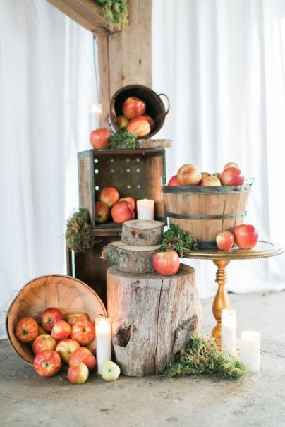 Pretty-woodland-and-rustic-decor-with-apples-in-wooden-baskets-moss-tree-slices-and-stumps-candles-on-the-floor