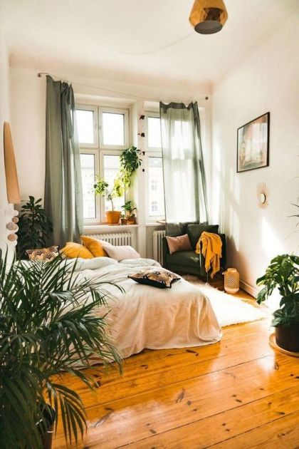 Ein-Boho-Schlafzimmer-mit-grünen-senffarbenen-Textilien-Kerzenlaternen-Topfpflanzen-und-eingängigen-Lampen