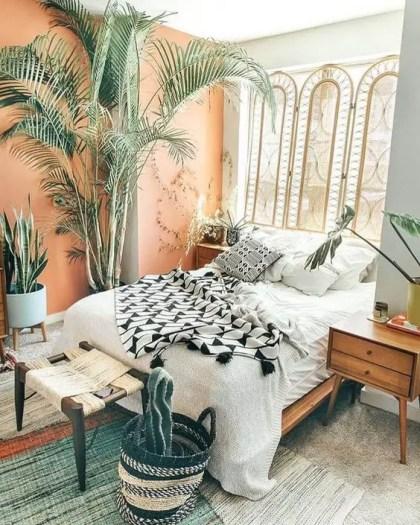 Ein-helles-boho-schlafzimmer-mit-einem-rattan-schirm-holzmöbel-einer-pfirsichfarbenen-wand-topfpflanzen-und-grün-und-einem-korbhocker