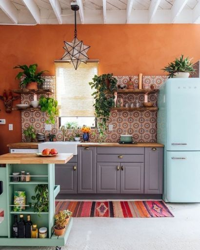 A-bright-kitchen-with-orange-walls-a-bright-printed-tile-backsplash-a-blue-fridge-a-green-kitchen-island-and-potted-greenery
