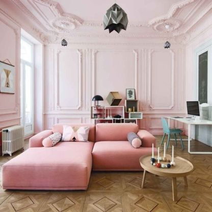 A-gorgeous-blush-living-room-with-molding-a-pink-sofa-a-creative-storage-unit-and-a-working-space-at-the-wall
