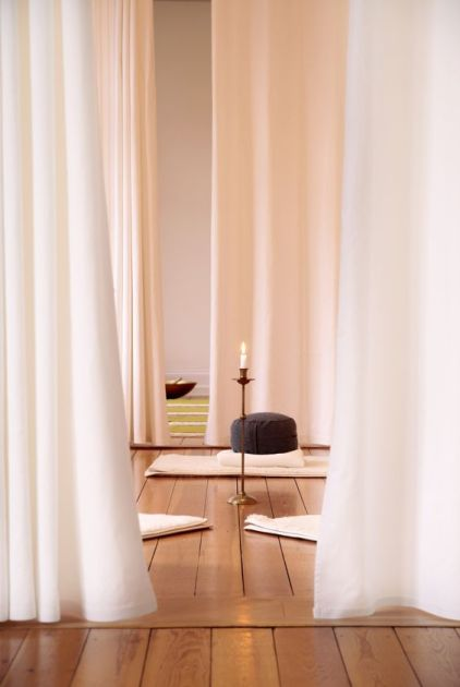 Ein-minimalistischer-meditationsraum-mit-vorhang-teppichen-kissen-und-kerzen-in-kerzenhaltern