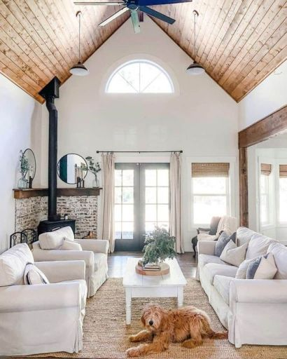 A-modern-country-living-room-with-a-hearth-neutral-furniture-a-highlit-slanted-ceiling-printed-and-neutral-textiles