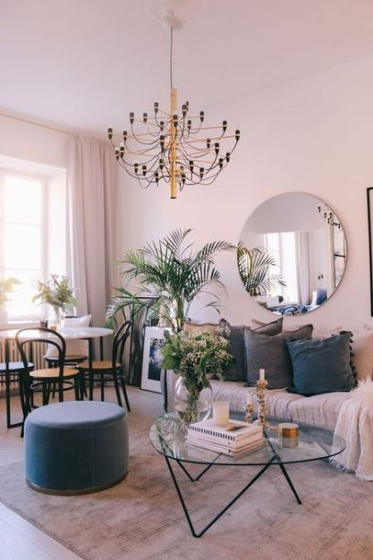 A-soft-living-dining-room-with-blush-walls-a-round-mirror-a-chic-chandelier-touches-of-grey-and-navy