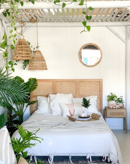 A-boho-tropical-bedroom-done-in-neutrals-a-white-wooden-ceiling-woven-pendant-lamps-and-a-cool-rattan-headboard-plus-lots-of-greenery
