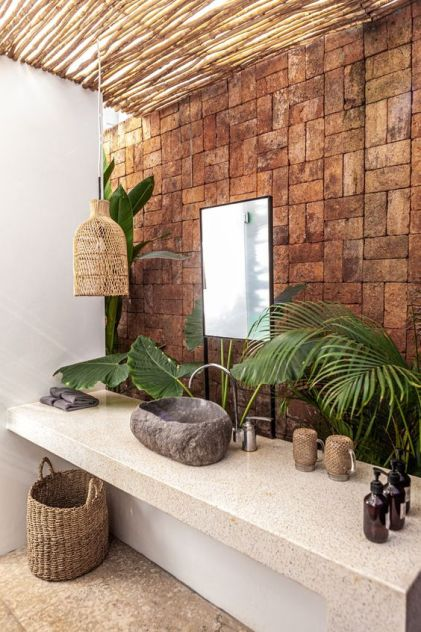 A-catchy-tropical-bathroom-with-a-brick-wall-a-stone-vanity-a-stone-sink-a-woven-lamp-and-a-basket