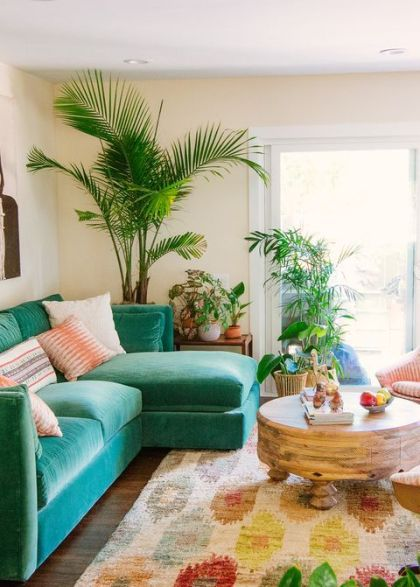 A-colorful-tropical-living-room-with-an-emerald-sofa-a-colorful-boho-rug-potted-plants-and-a-round-wooden-table