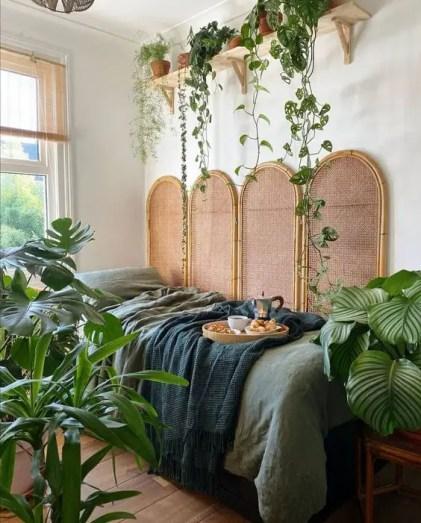 Ein-Dschungel-Themen-Schlafzimmer-mit-einem-Rattan-Bildschirm-grüne-Beet-Statement-Topfpflanzen-und-Kletterpflanzen