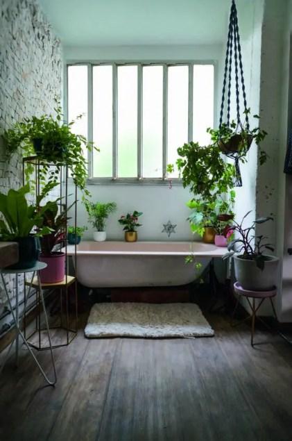 Ein-hübsch-stimmungsvolles-Badezimmer-mit-einer-rosa-Wanne-bunte-Pflanzgefäße-mit-Grün-rundum-und-einer-Ziegelmauer-für-Interesse