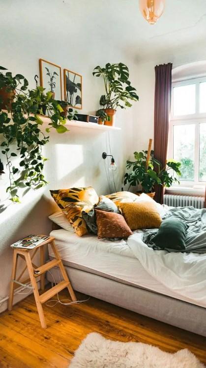 Ein-entspanntes-Boho-Schlafzimmer-in-Neutralen-mit-bunten-Textilien-Topfgrün-und-Kletterpflanzen-ist-sehr-gemütlich