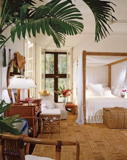 A-tropical-bedroom-with-a-jute-rug-a-bamboo-bed-with-a-canopy-wooden-furniture-and-shutters-plus-tropical-plants