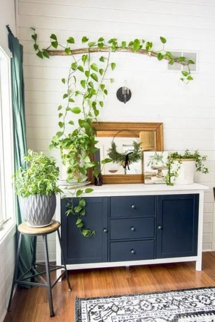 Ein-Vintage-Sideboard-mit-etwas-Topf-Grün-ein-Stock-und-Grün-Installation-drüber-und-einem-grauen-Pflanzer-mit-Grün