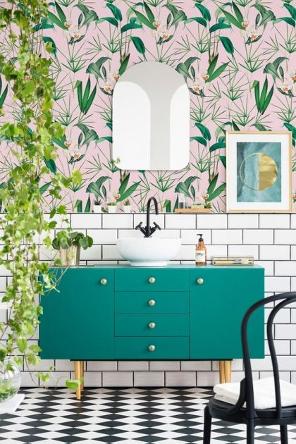 An-airy-and-fun-tropical-bathroom-with-catchy-wallpaper-a-green-vanity-cascading-greenery-and-touches-of-gold