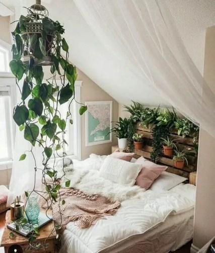 Ein-Dachboden-Boho-Schlafzimmer-in-Neutralen-mit-einer-Palette-vertikaler-Garten-eine-Kletterpflanze-in-einem-Käfig-und-einem-gemütlichen-Bett