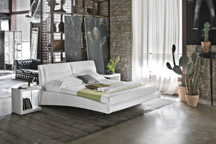 Leaning-portraits-cacti-exposed-brick-bedroom