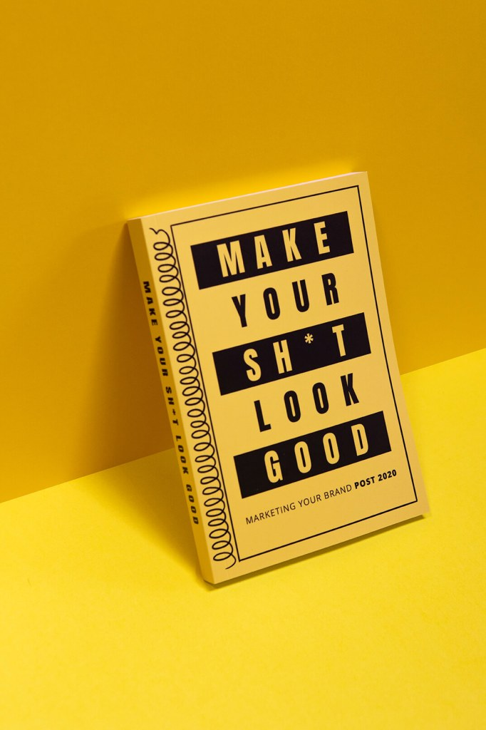 One Make Your Sh*t Look Good book leaning upright against a yellow wall
