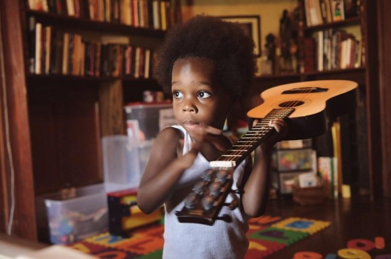 Black boy holding guitar over his shoulder black kids music article